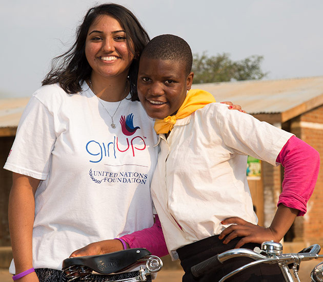 United Nations Girl Up girls smiling with a bicycle