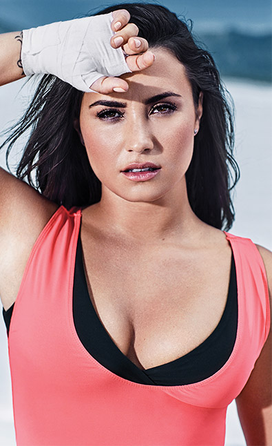Demi Lovato wearing a pink and black fabletics top